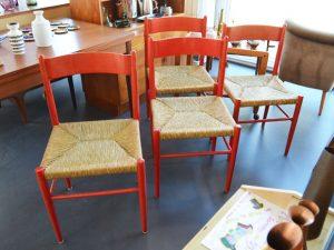 Vier rote Stühle mit Binsengeflecht